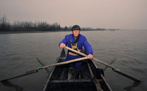 Zhang rows a boat on Dongting Lake, on his mission to prevent wild birds from being poached and trapped. (China Photo Press/Tong Di)