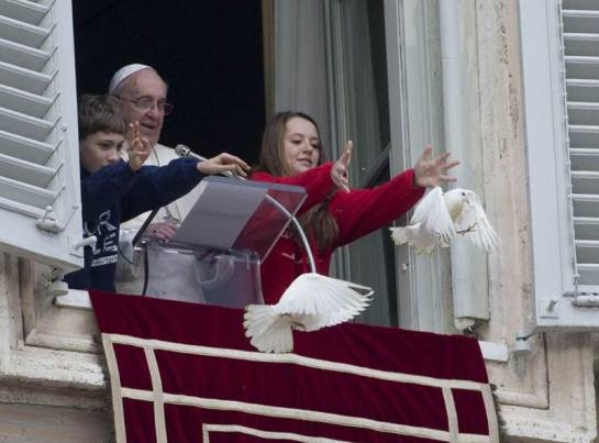 Pope Francis and two children release doves from the window of his studio overlooking St. Peter's Square.